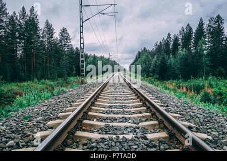 Finland, Railroad tracks whit electricity grid for the locomotives on a cloudy day - Stock Photo