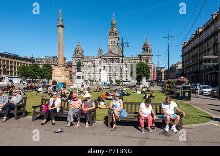People out enjoying a pleasant sunny evening in George Square, central Glasgow, with the City Chambers in the background, the cenotaph, and statues, - Stock Photo