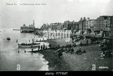 Postcard showing a print of Herne Bay (Kent, England) looking east from the third Herne Bay Pier. The original photo was probably taken from the promenade deck halfway up the Grand Pier Pavilion, or possibly from the roof of the entrance building. This shows a special aspect of the pier, which was to give an unusual view of the town from the sea, for those who had no access to ships. The bandstand can be seen along the beach. It was published by Photochrom of London and Tunbridge Wells. 1924-1929 (Reason for date: 1924 first phase of bandstand is visible; 1932 second phase not yet visible; 192 - Stock Photo