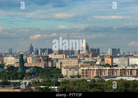 MOSCOW, RUSSIA - SATURDAY, JULY 7, 2018: Fan Fest Moscow, Vorobyovy Gory near Moscow State University. Fans watch FIFA games on large screens here. Cheerful mood, beautiful cityscapes. The area capacity is more than 30000 people. Football lovers from many countries meet here. People watch England vs Sweden game and are getting ready for Russia vs Croatia game. City view from Vorobyovy Gory (Sparrow Hills). Tall building of the Russian Ministry of Foreign Affairs (center). Credit: Alex's Pictures/Alamy Live News - Stock Photo