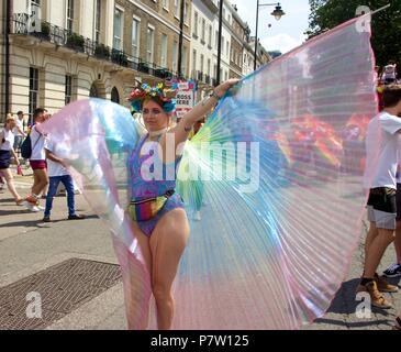 London, UK. 7th July 2018. A woman in a swimming costume and a rainbow coloured sheer cape at Pride in London 2018 Parade, joining more than 1 million attending the march today to celebrate LGBT+. Credit: Dimple Patel/Alamy Live News - Stock Photo