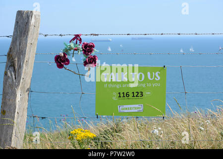 Culver Down, UK. 07th July, 2018. A Samaritans sign on the edge of Culver Cliff on the Isle of Wight, UK, reads, 'Talk To Us if things are getting to you' - posted after a spate of suicides from the same spot. Yachts can be seen passing in the background during the 'Round The Island Yacht Race' on the hottest recorded day of the year so far at 33 degrees Celcius. Credit: Matthew Blythe/Alamy Live News - Stock Photo
