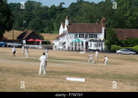 Tilford, Surrey, UK. 8th July, 2018. As the heatwave continues, people were having fun in the sun on a beautiful Sunday afternoon in the pretty village of Tilford. Many were cooling off in the river or sunbathing, while a cricket match was being played on the village green. Credit: GP Images/Alamy Live News. - Stock Photo