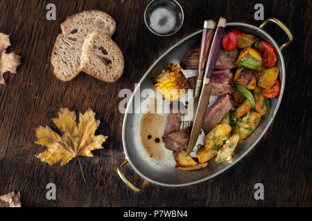 Beef steak with fried potatoes and vegetables in frying pan on dark background, top view. Dinner table concept - Stock Photo