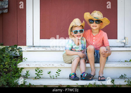 Mixed Race Chinese and Caucasian Young Brothers Having Fun Wearing Sunglasses and Cowboy Hats - Stock Photo