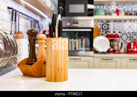 Kitchen knives in a special wooden stand with spice jars. Close-up. Kitchen concept - Stock Photo