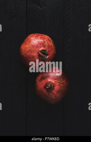 Flat lay of two ripe pomegranate fruit on black wooden vintage background. Top view with copy space. - Stock Photo