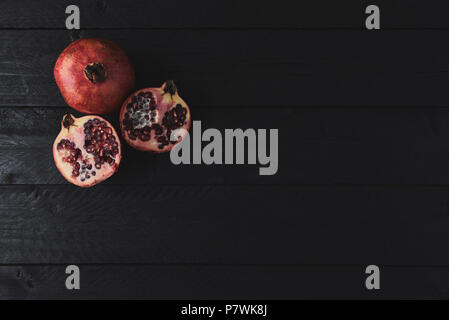 Flat lay of ripe pomegranate fruit on black wooden vintage background. Top view with copy space. - Stock Photo