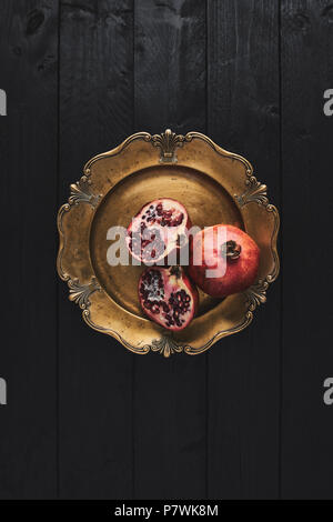 Flat lay of ripe pomegranate fruit on an old golden serving plate, black wooden vintage background. Top view with copy space. - Stock Photo