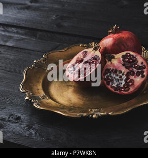 Ripe pomegranate fruit on an old golden serving plate, black wooden vintage background. Narrow depth of field, square crop, copy space. - Stock Photo