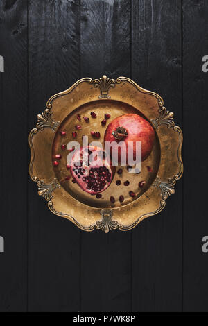 Flat lay of ripe pomegranate fruit surrounded by seeds on an old golden serving plate, black wooden vintage background. Top view with copy space. - Stock Photo