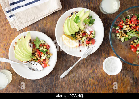 Tasty and healthy vegetarian food. Salad of black quinoa, chickpeas and vegetables with avocado bruschetta on a wooden table with lemonade, top view - Stock Photo
