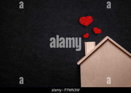 Home sweet home with red heart. Wooden house and Black leather background. Happy family lifestyles and Loving people concept. Future asset between us  - Stock Photo