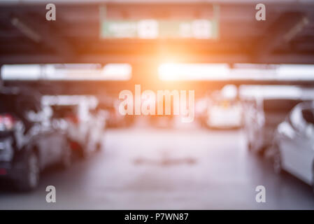Blurry of car parking lots at department store with orange sun light. Abstract and transportation concept. - Stock Photo