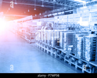 Blurry background of warehouse and storage. Abstract of business concept. Logistics and industrial theme. Blue tone and orange sun light element - Stock Photo
