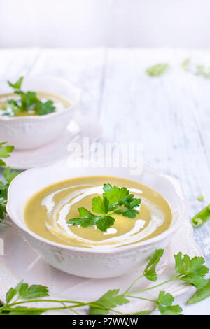 Cream soup with green peas and fresh herbs. Summer dinner. Healthy diet . Soup from vegetables. Free space for text. Vertical photo - Stock Photo