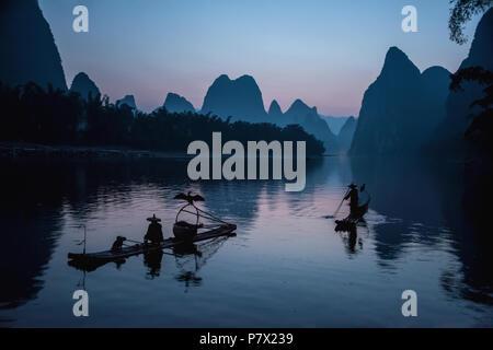 Cormorant fishermen pre-dawn in a quiet time before starting to fish, Li River, China