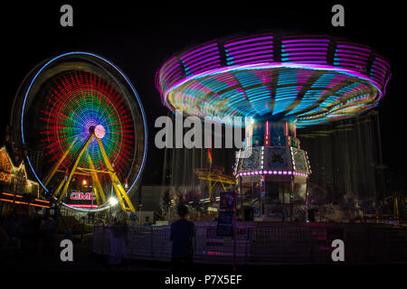 Brightly coloured, motion-blurred Ferris wheel and swing rides and ghostly people at the Calgary Stampede Midway located in Calgary, Alberta, Canada. - Stock Photo