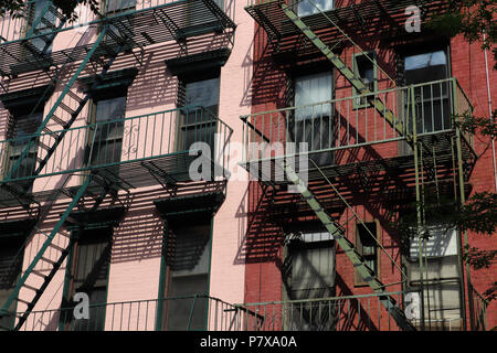 Close up of two old brick buildings in lower Manhattan painted pink and red, with green fire escapes that cast interesting shadows on their facades - Stock Photo
