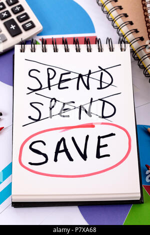 The word Save circled in red below a list of spending written on a notepad surrounded by pencils, graphs, books and calculator. - Stock Photo