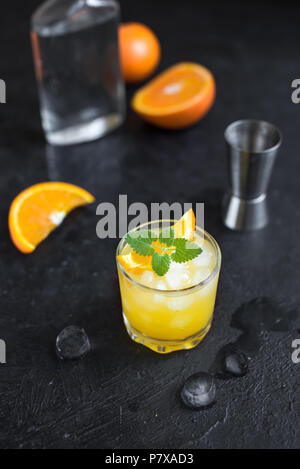 Gin and orange juice cocktail on black background. Refreshing summer cocktail with vodka, ice, orange and mint. - Stock Photo