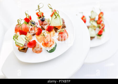 Assortment of canapes. Banquet service in restaurant . Catering food, snacks on white plate - Stock Photo