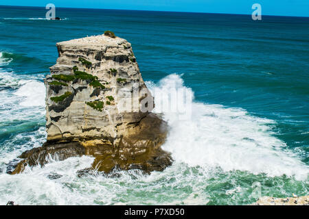 Wave crashes into rocky outcrop in gannet colony - Stock Photo
