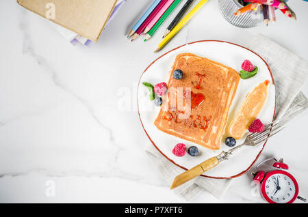 Back to school kids breakfast concept, pancakes with raspberry jam - I love school, on white marble stole, with books, alarm clock, pencils, school su - Stock Photo