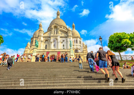 Paris, France - July 3, 2017: tourists climb up the steps leading to Basilica of Sacre Coeur de Montmartre in Paris in a sunny day with blue sky. Sacred Heart Church is a popular tourist landmark. - Stock Photo