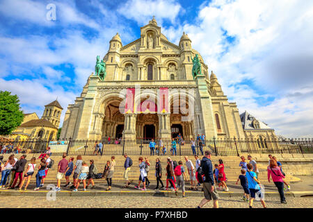 Paris, France - July 3, 2017: people in a row in front of facade of Basilique du Sacre Coeur de Montmartre. Sacred Heart Church of Paris with tourists. Popular religious attraction in Paris. - Stock Photo