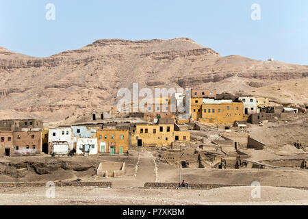 Modern Egyptian houses built over the ruins of Deir el-Medina, the ancient village of artisans who worked at the Valley of the Kings, Luxor, Egypt. - Stock Photo