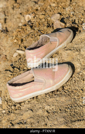 abandoned or forgotten shoes on the beach. - Stock Photo