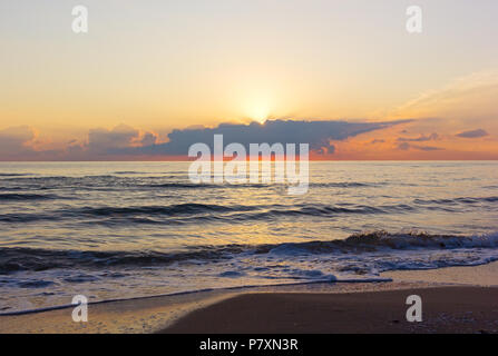 Sun arises from the clouds over Mediterranean Sea in Valencia region of Spain. Cloudy sunrise in orange hues over the calm sea. - Stock Photo