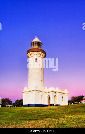Pink blue sunrise over Norah Head lighthouse on Australian Central coast - top of the hill with green grass around historic landmark building. - Stock Photo