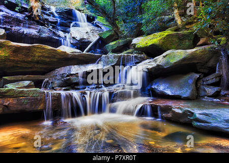 Smooth waterfall flowing down cascade of sandstone rocks in deep rainforest creek near SOmersby on Australian Central coast. - Stock Photo