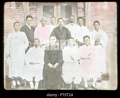 English: Group portrait of Fr. John E. Morris, MM, and eleven Korean men, Korea, ca. 1920/1940 Colorized lantern slide of Fr. John E. Morris, MM, with eleven Korean men. Fr. Morris wears a cassock and glasses. He is one of four men seated in the front row. The two men to his left have their arms crossed over their chests. Standing in the back row on the right hand side is a man holding a book. The group poses in front of the door to a brick building.  Photographer: Unknown Subject (keyword): indigenous peoples; clergy; group portraits Filename: MFB-LS0488 Coverage date: circa 1920/1940 Subject - Stock Photo