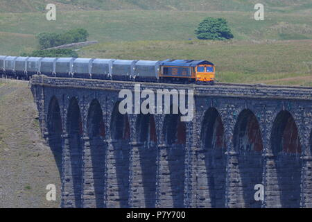 A Great British Rail Freight (GBRf) train crosses the imressive victorian engineered Ribblehead Viaduct in North Yorkshire