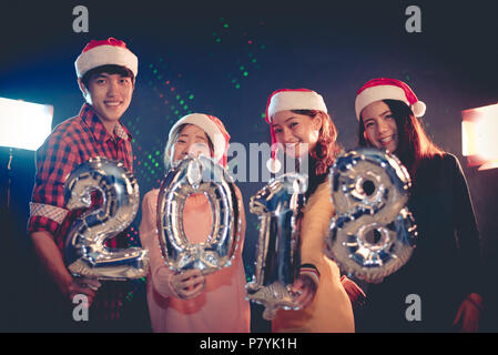 Asian people who wearing Santa hat celebrating New year party 2018 and showing alphabets balloon in night pub or bar. Christmas and New year 2018 conc - Stock Photo