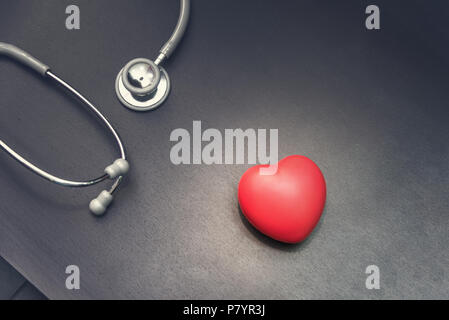 in top view, Red heart with stethoscope medical equipment on the doctor desk background. Medical and Health care concept, Hospital and Emergency theme - Stock Photo