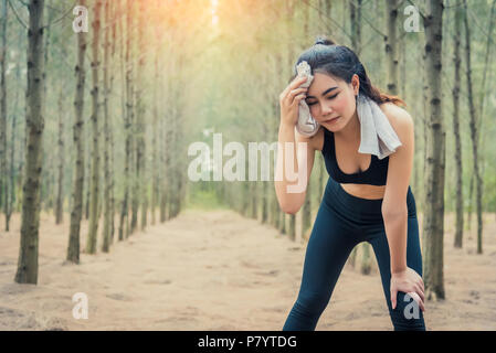 Asian beauty woman wiping the sweat in forest. Towel and sweat elements. Sport and Healthy concept. Jogging and Running concept. Relax and take a brea - Stock Photo