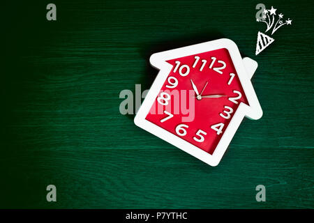 Home shape red clock on green floor background with celebration firework icon. Happy life and Family concept. Interior and Object theme. Time in daily - Stock Photo