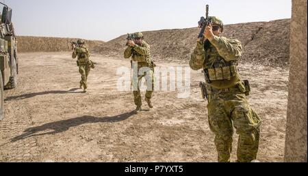 Australian soldiers, with Task Group Taji's quick reaction force, demonstrate building clearance drills during concurrency training with U.S. Soldiers of Bandit Troop, 3rd Calvary Regiment at Camp Taji, Iraq, June 11, 2018. A Coalition created from a diverse international community will continue its support to the people of Iraq in order to enhance the capabilities of the nation to ensure security and stability. (U.S. Army photo by Spc. Audrey Ward) - Stock Photo