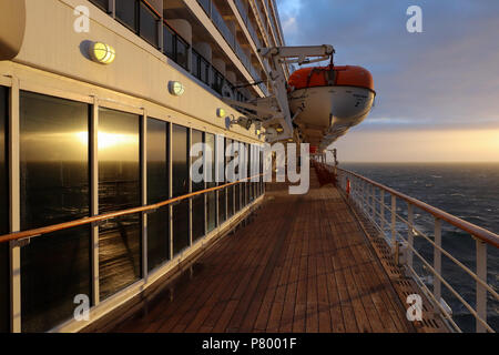 Evening on deck 7 of the Queen Mary 2 as the setting sun comes from behind the clouds to illuminate the deck and sea; life boats hand above deck. - Stock Photo