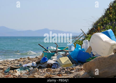 plastic garbage and wastes on the beach with the sea and an island on background - Stock Photo