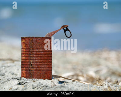 Rusty tin can on the beach with blue sea - Stock Photo