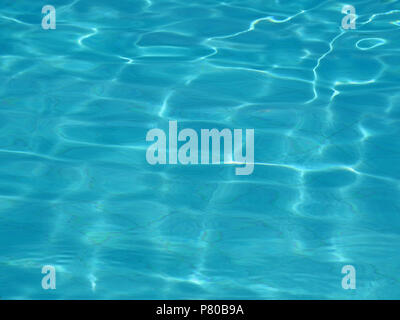 water surface of a swimming pool with sun reflections - Stock Photo