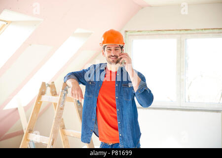 Handsome young repairman using his mobile phone while standing in the house and working on interior repairs. - Stock Photo