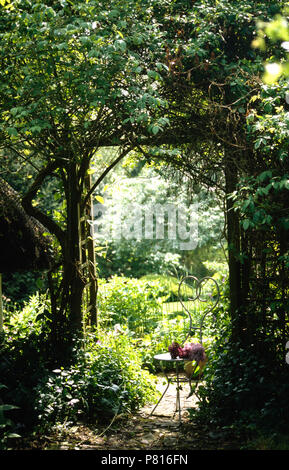 Ornate wrought-iron chair against trellis arch with green climbing plants and view of country garden - Stock Photo