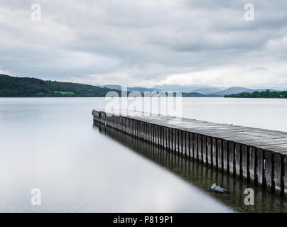 Pier stretching out into the calm waters of Lake Windermere at Miller Ground in the Lake District with the Langdale Pikes in the distance - Stock Photo