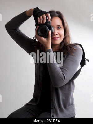Female photographer posing with a camera - Stock Photo